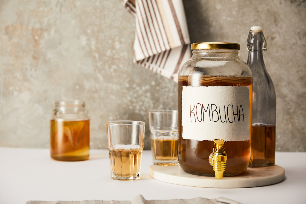 jar with kombucha near glasses and bottle on textured grey background with striped napkin