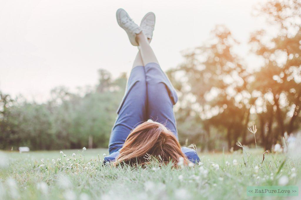 vrouw voelt zich gelukkig liggend op het gras in het park met vintage toon. onderwerp is wazig en low-key.