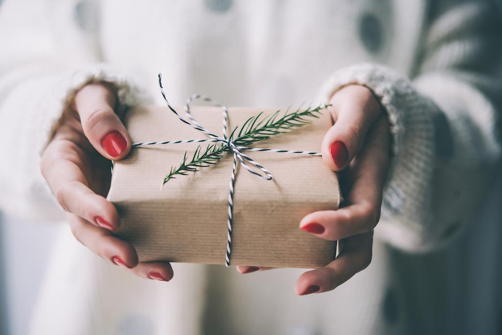 Vrouwenhanden houden kerst- of nieuwjaarsversierde geschenkdoos. Afgezwakt beeld
