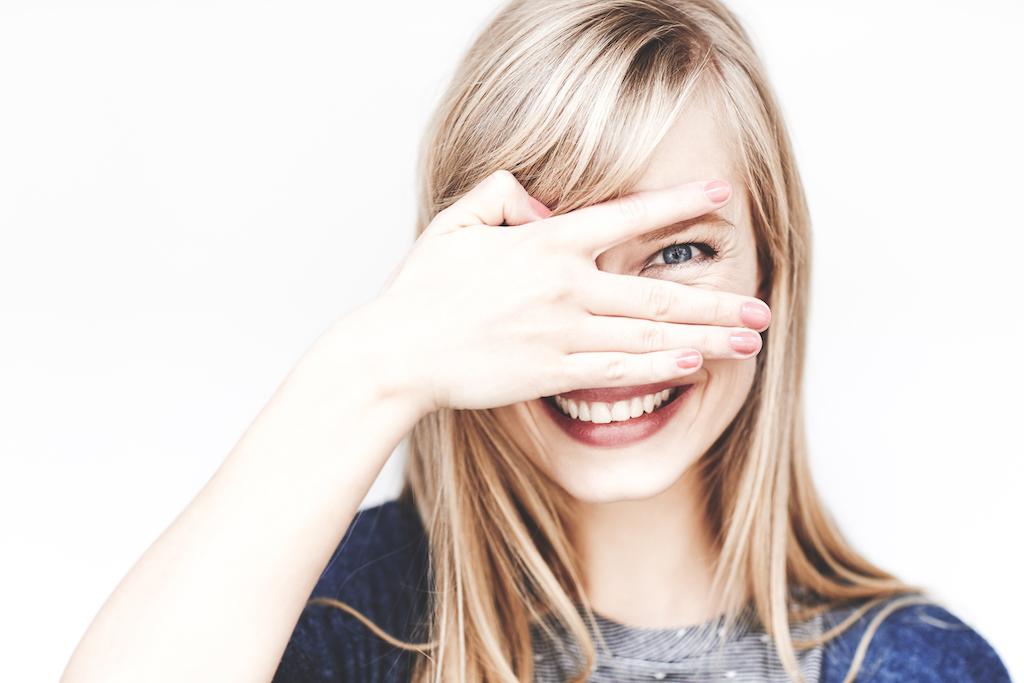 gluren jong blond vrouw glimlachen in camera